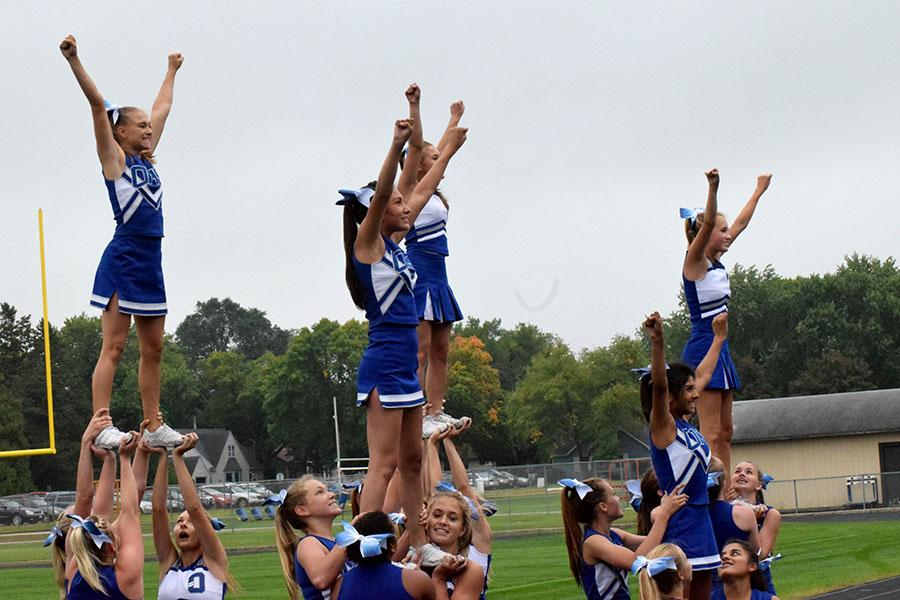 Owatonna cheerleading performing a stunt during the pepfest