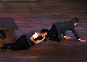 Helena (Maureen Gleason) clings to Demetrius' (Jackson Anderson) leg to stop his escape on stage.