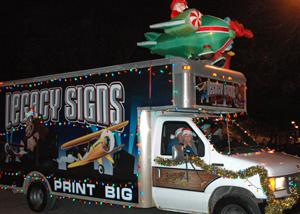 Local business Legacy Signs shows off their Christmas spirit during the parade on Thursday for the Festival of Lights.