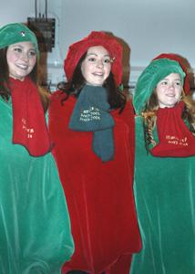 Junior Anna Moe, senior Maureen Gleason, and junior Hannah Valen perform with the Owatonna Carolers on Thursday at the Festival of Lights.