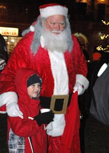 A child poses for a photo with Santa on Thursday for the Festival of Lights in Central Park.