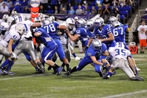 The Owatonna Huskies run a play against the Brainerd Warriors.
