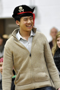 Snow King Ryan Huang stands in front of the crowd after accepting his pirate hat crown
