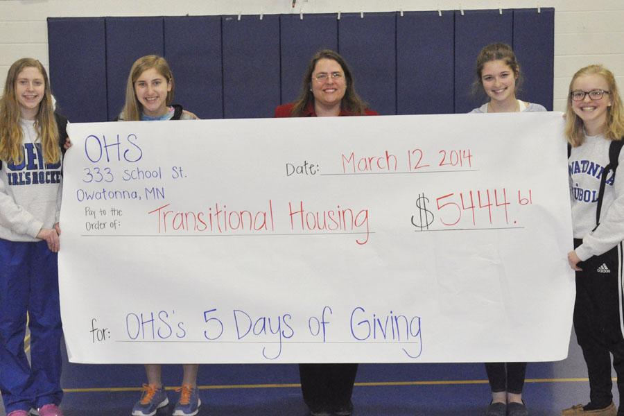 Julie Anderson from Transitional Housing receives the money from the OHS student body