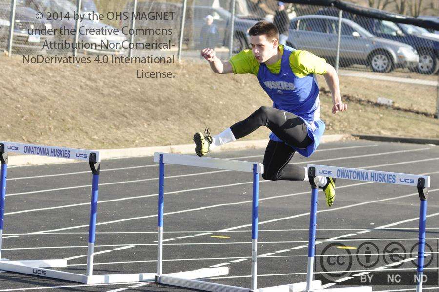 Jacob Johnson springs over the hurdles, placing 2nd for Owatonna