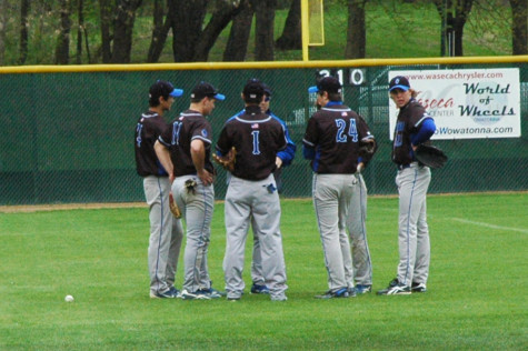 A few team members have a meeting with their coach in the outfield