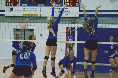 Senior Allison Falken and junior Elise Oppegard putting up a block at the net