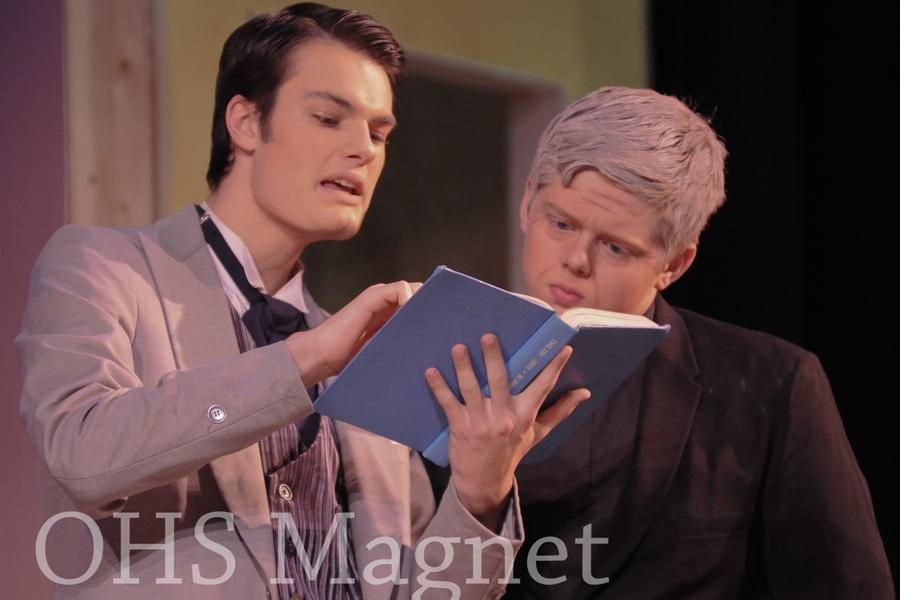 John Worthing (Thomas Donlon) and Reverend Chasuble (Ethan Pick) anxiously look through the army ledger
