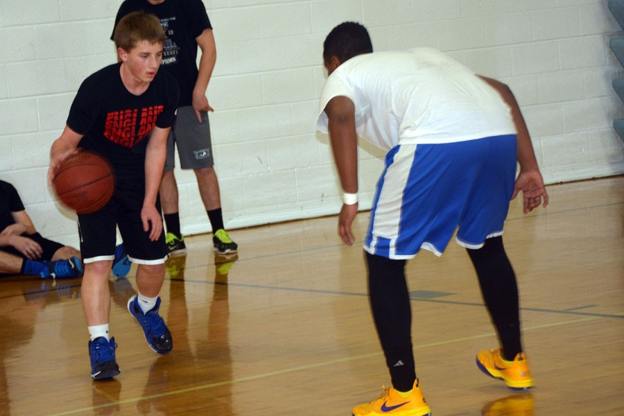 Sophomore Daniel Keller (left) dribbles up the court as senior Ahmed Mohamud (right) plays defense