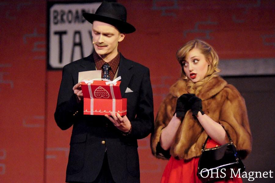 Miss Adelaide (Jessica Friedman) gives Nathan Detroit (Matt Reinhard) a belt to celebrate their 14 years of engagement