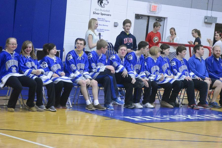The Adapted Floor Hockey team smiles as they receive hearty applause from their peers