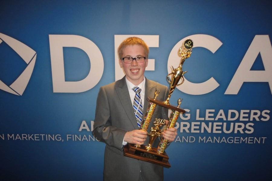 Senior Jack Livingston poses with his trophy from DECA State