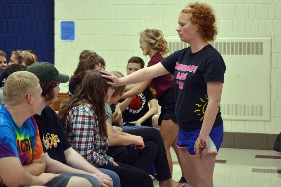 Junior Kaitlyn Skalicky petting an audience members hair after being tricked into believing that she is at a petting zoo