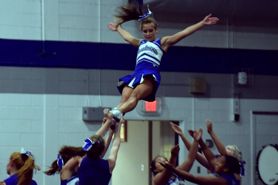 Sophomore Angela Wishy performing a stunt during the cheer performance
