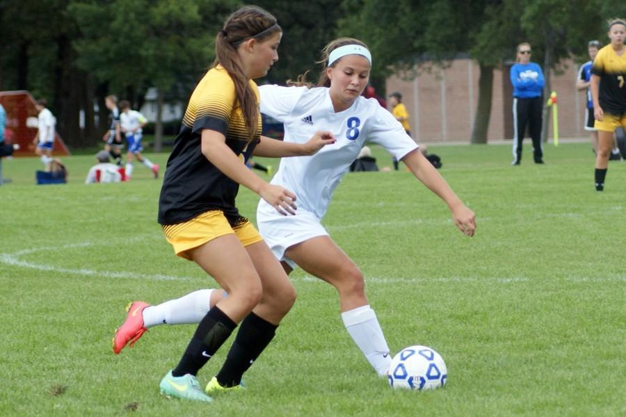 Junior Toria Koch battles a Burnsville player for the ball