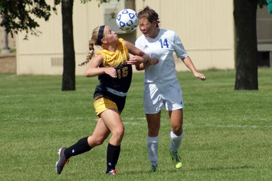 Junior Callie McCauley battles defender to head the ball