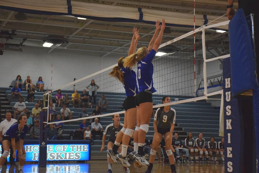 Sophomore Sydney Schultz and junior Karissa Gregory blocking the incoming ball