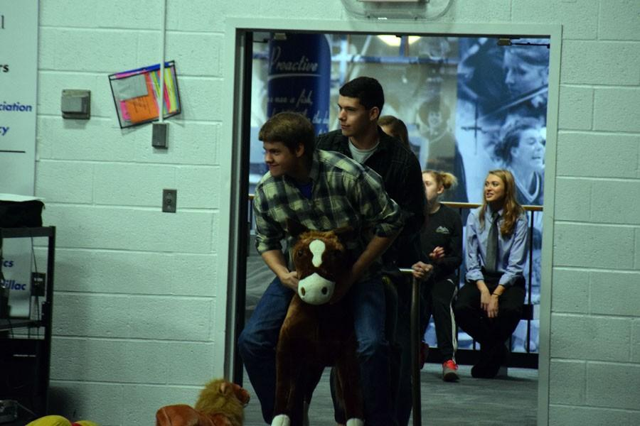 Seniors Ryan Guenther and Tyler Kain riding a horse into the Snow Week Pepfest