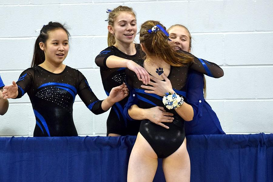 Becca Olson gets a hug from her teammates after competing