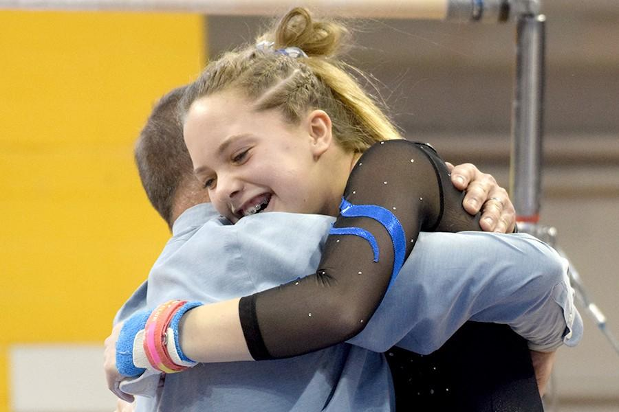 Lindsay Bangs receives a hug from Coach Tom Smith after competing