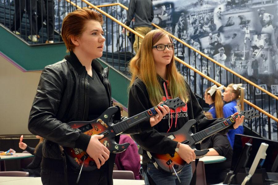 Freshman Kenna DaMitz and Jessica Pieper playing guitar hero for rock day