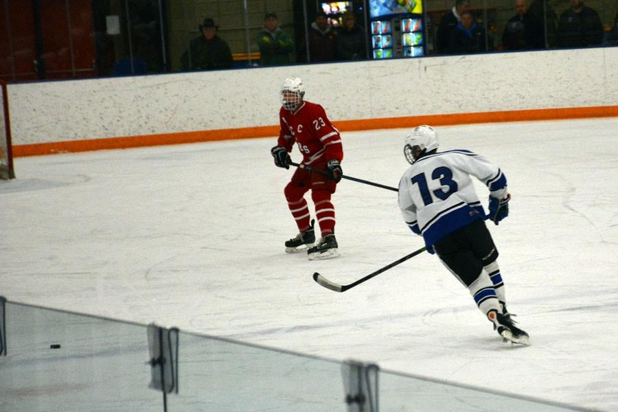 Alec Holcomb chases the puck into the offensive zone