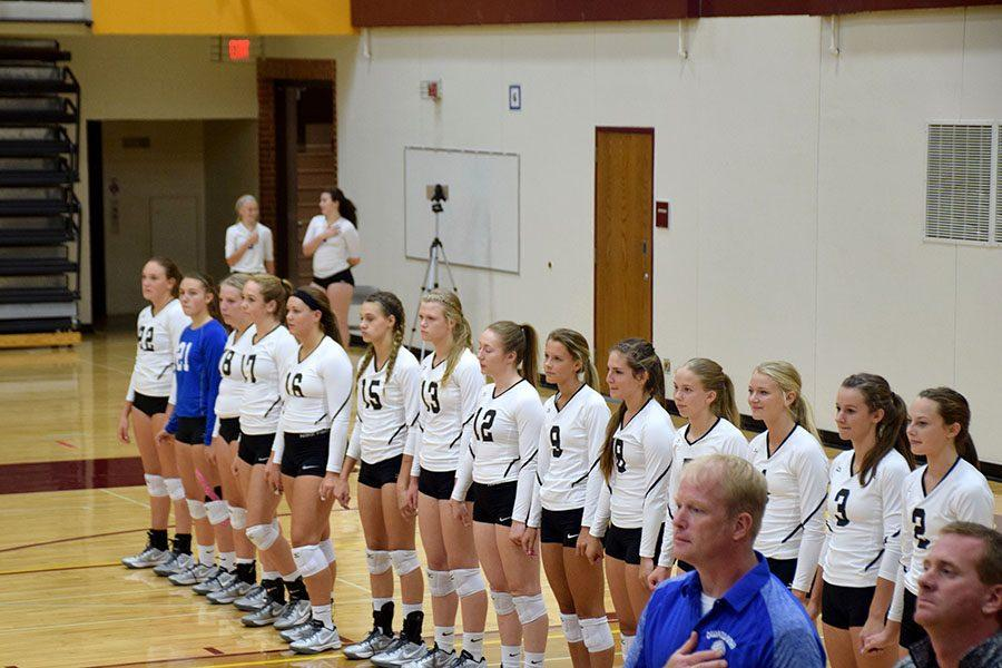 Owatonna Volleyball team lining up for the national anthem before the game