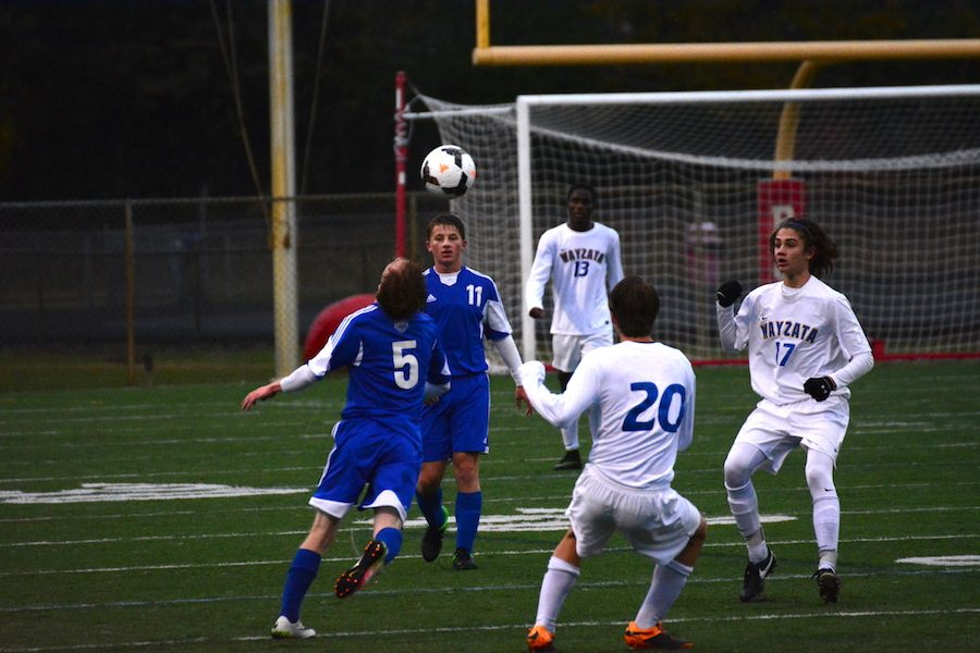 Junior Spencer Glynn heads the ball off of a throw in