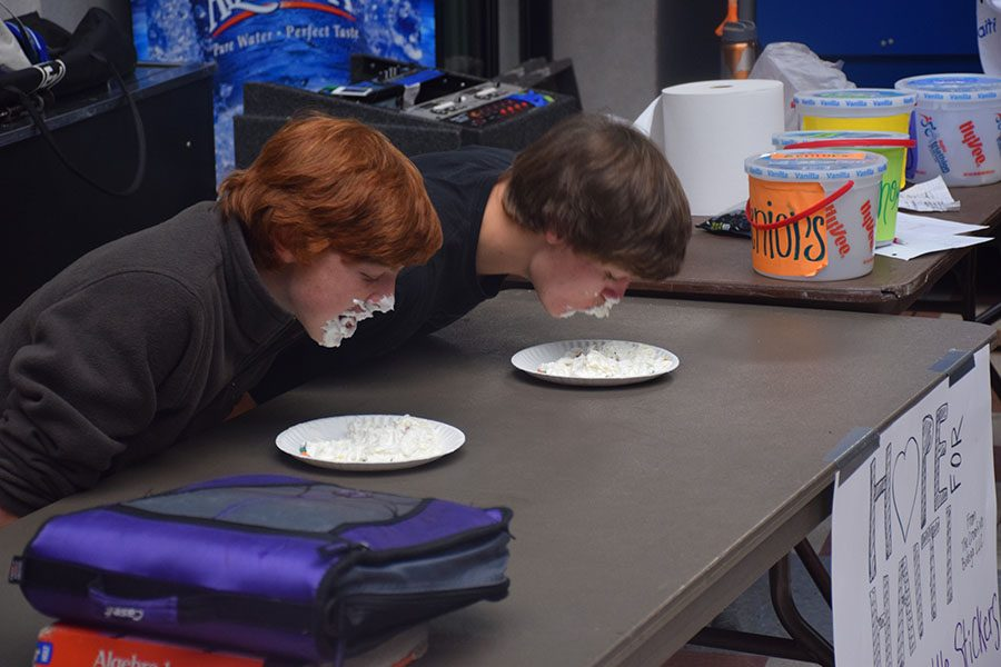Junior Parker Westphal and Freshmen Phillip Koslosky dive face first into the whip cream.