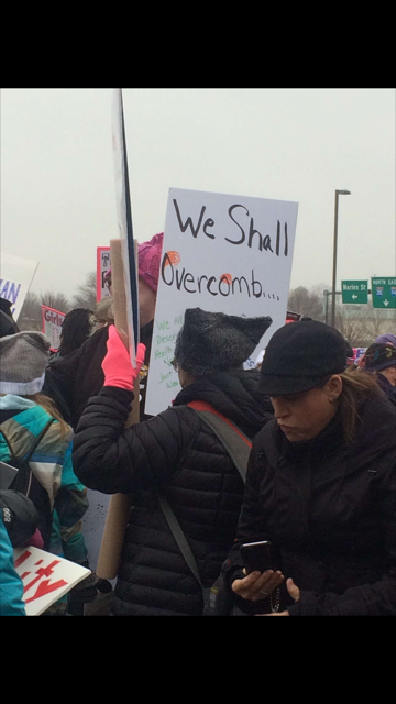 A woman holds up a sign that says