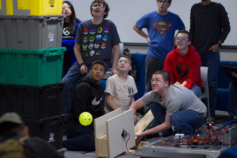 Owatonna Robotics Team members testing a prototype wiffle ball shooter