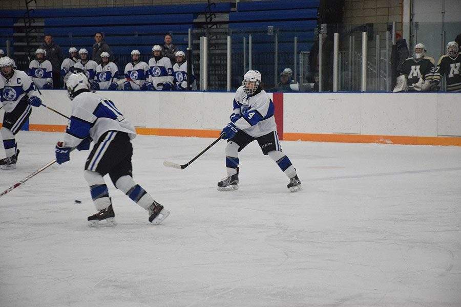 Junior Nate Smith passing the puck to Mitch Wiese