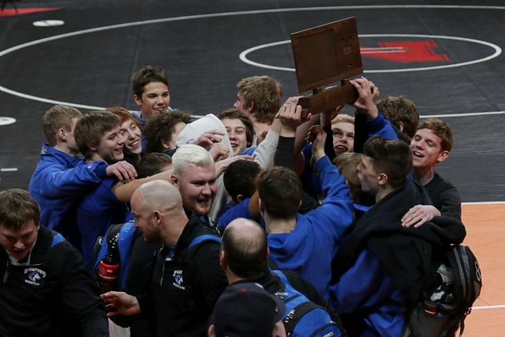 The Owatonna wrestling team holds up their consolation trophy