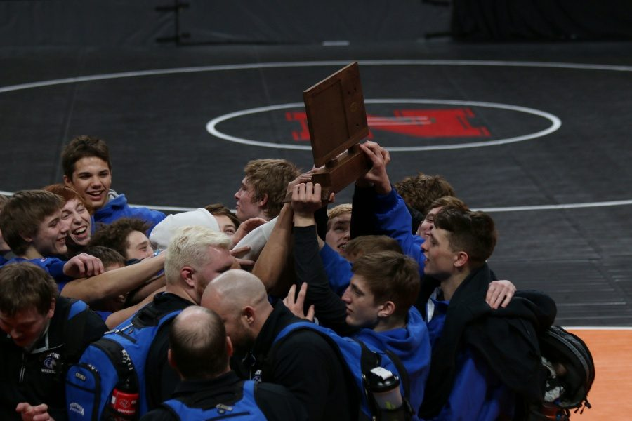 OHS Wrestlers hold up the Consolation trophy in celebration at the Excel Energy Center