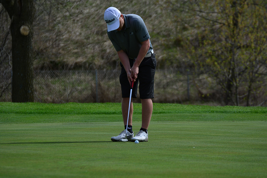 Senior Andrew Wall prepares to make a putt