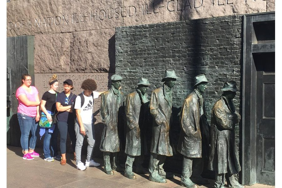 The students posing next to a memorial