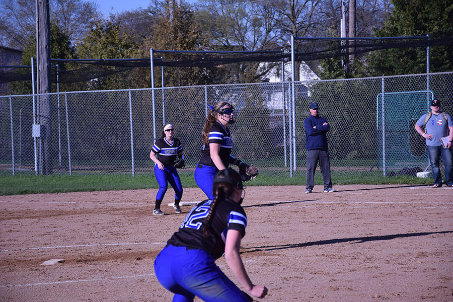 Junior Alexa Sommers Looks to pitch as teammates stand by for the pitch