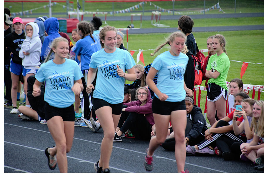 Senior Karrissa Gregory and Juniors Syd Schultz and Margo Achterkirch jogging at the big nine meet.