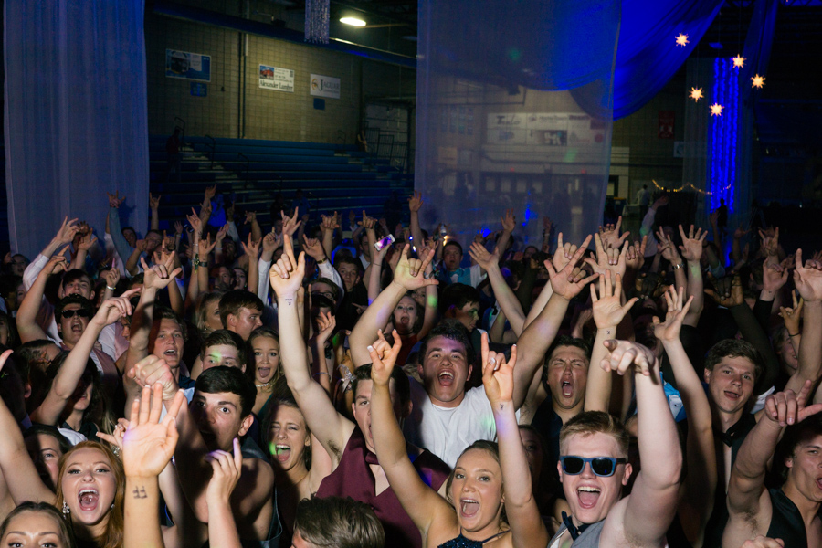 Prom goers throw their hands in the air for the camera
