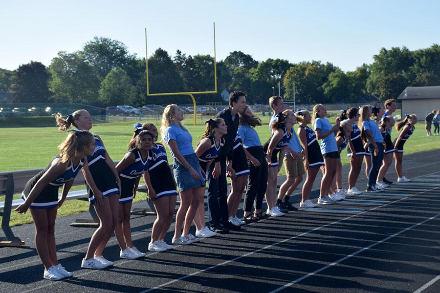 Cheerleaders and juniors partaking in a group cheer