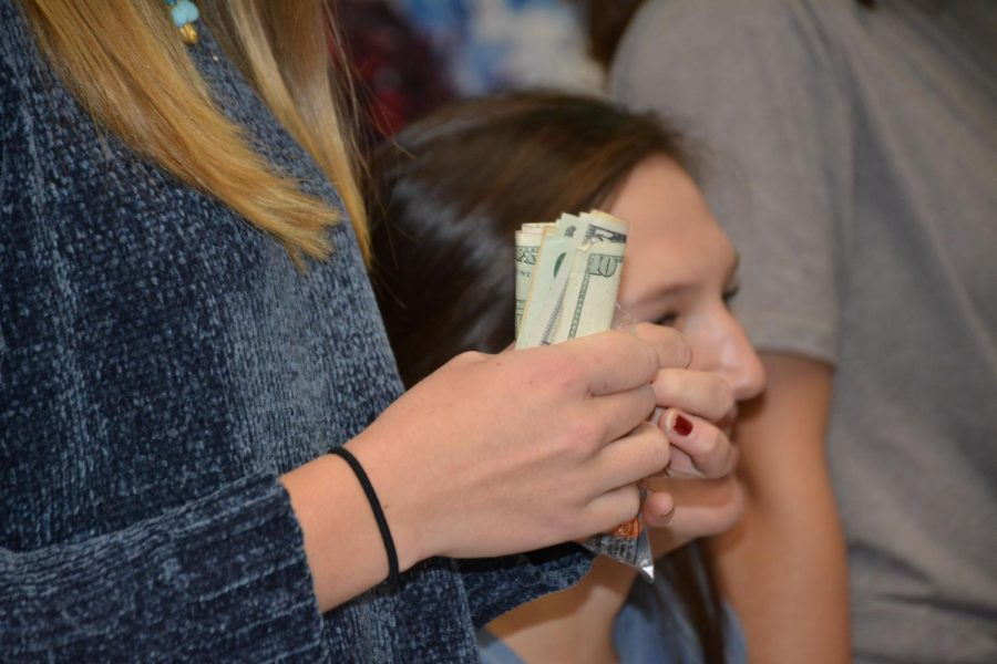 Sophomore Liv Larsen collecting cash for the Cash Drive.