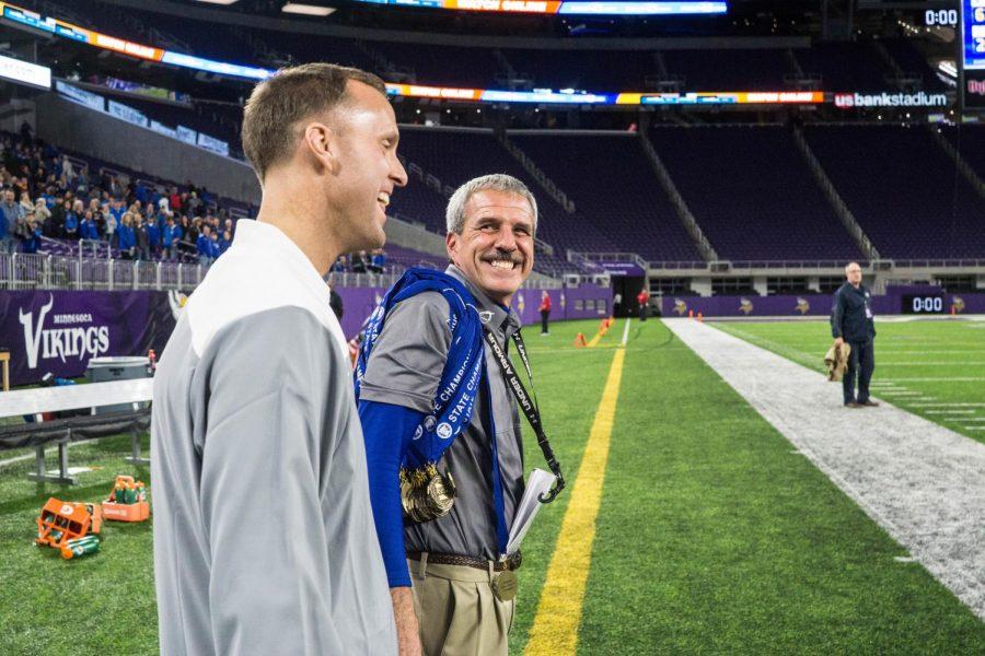 Principal Mark Randall congratulates coach Jeff Williams
