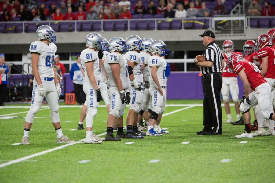 A referee visits with the O line after an Elk River penalty