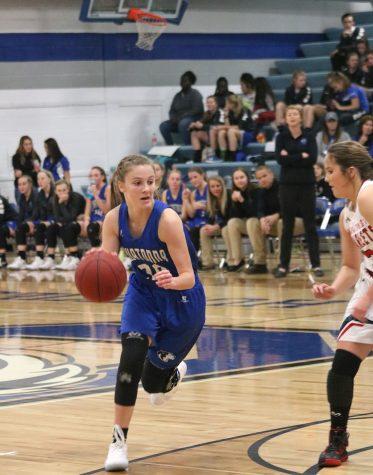 Jenna Zeman shielding the basketball from an opponent