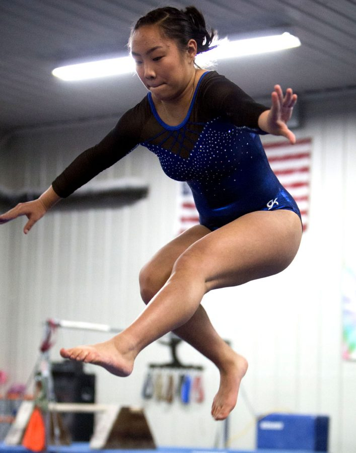 8th grader Lillie Bos preforming a wolf jump on the beam.