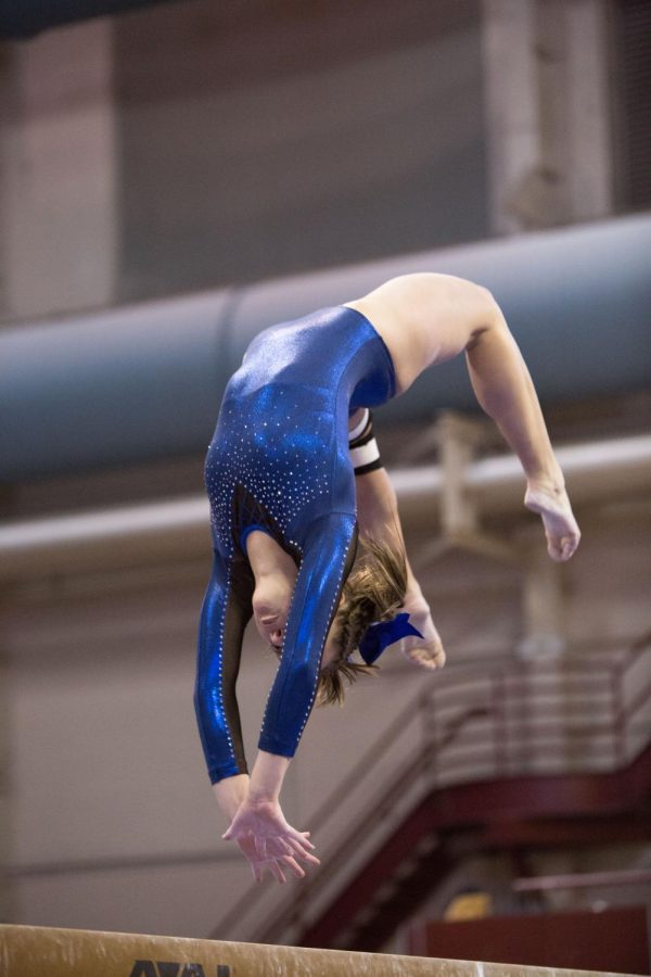 Lindsey Bangs flips while performing her beam routine