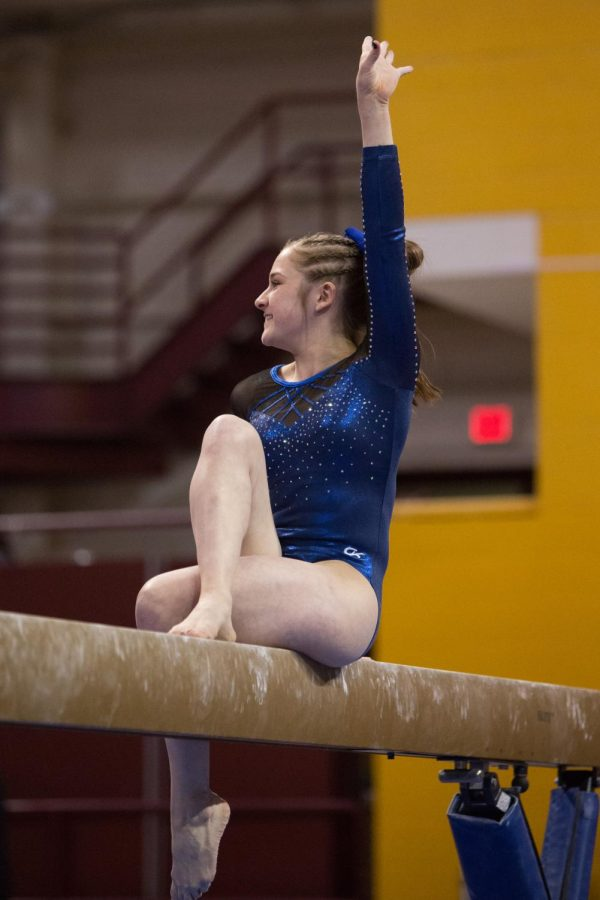 Becca Olson poses during her routine on beam