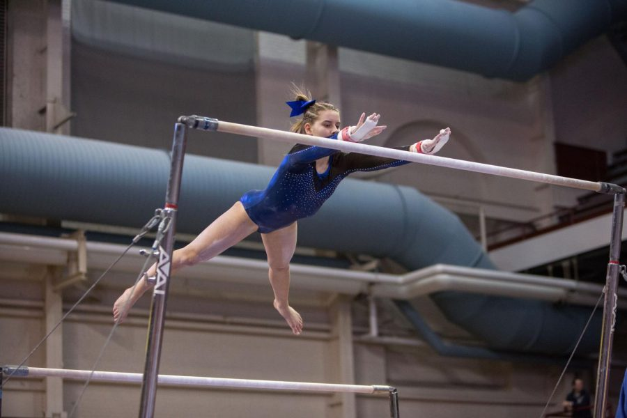 Freshman Lucy Matius leaping on the uneven bars