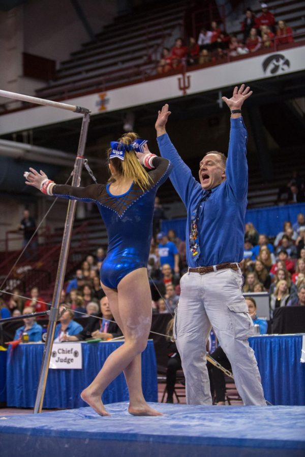 Coach Tom Smith reacts after senior Becca Olson sticks her bars routine