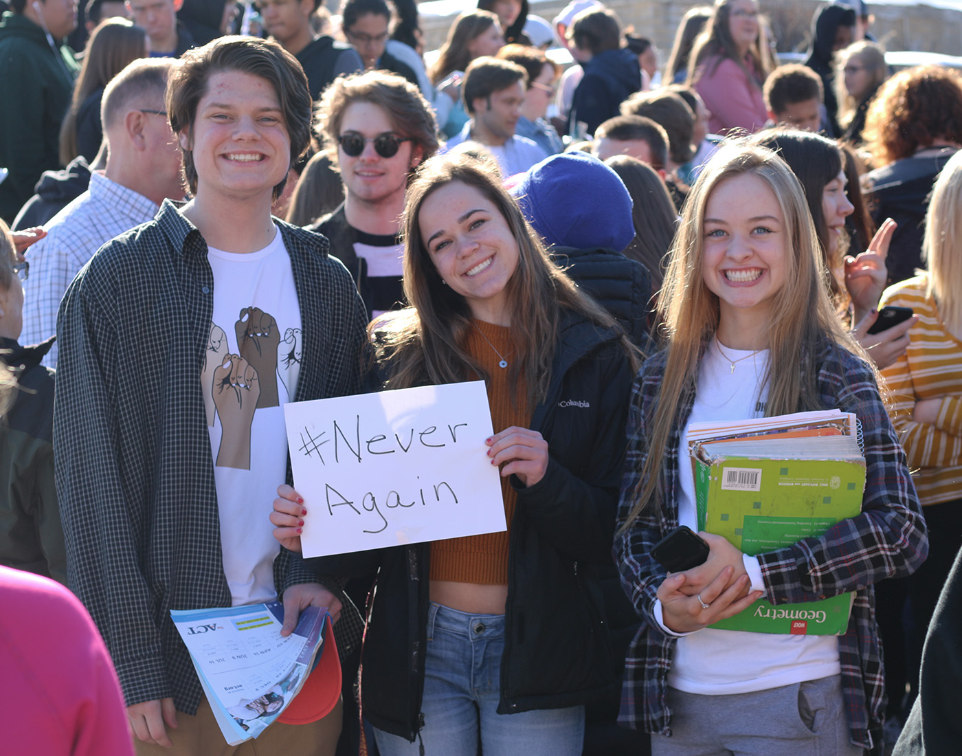 Noah Wagner, McKenzie Haberman and Cecilia Nicholson pose with a poster supporting #NeverAgain